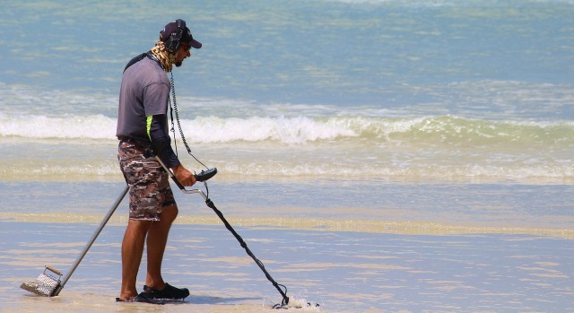 A man hunts for treasure on the beach with a metal detector