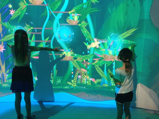 Two girls plant seeds in Connected Worlds, New York Hall of Science, 2015