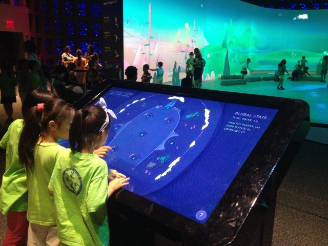 Kids examine the overview screen, Connected Worlds, New York Hall of Science, 2015